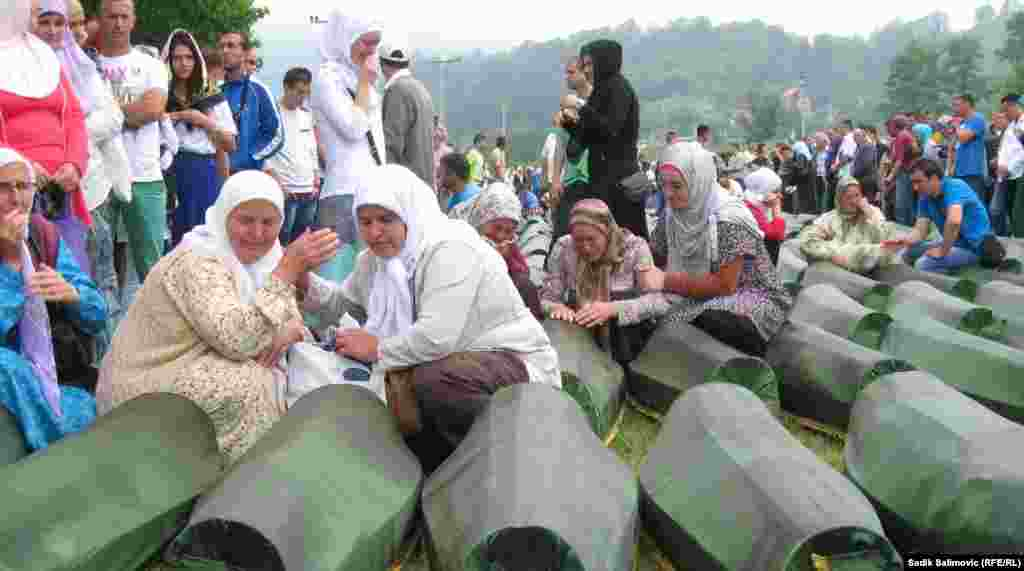 Bosnian women cry over the coffins of relatives, set to be reburied in Potocari, near Srebrenica.