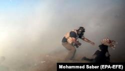 NOvinar pomaže demonstrantkinji nakon što je izraelska vojska ispalila suzavac na njih