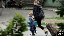 Жительница Луганска и ее дочь покидают свой дом во время перестрелки