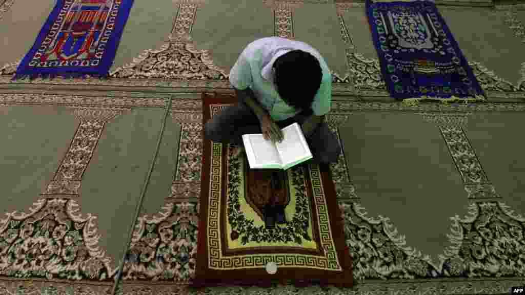 A man reads the Koran on a prayer mat at a mosque in Baghdad's northeastern suburb of Sadr City on July 16. (AFP/Ahmad Al-Rubaye)