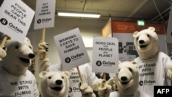 "Activists in polar bear costumes as they prepare for a ""Save Humans Too"" demonstration in Copenhagen."