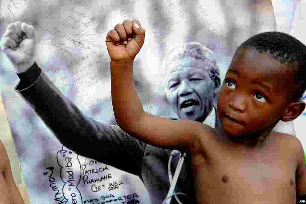 A young member of the Maitibolo Cultural Troupe poses in front of a picture of Mandela.