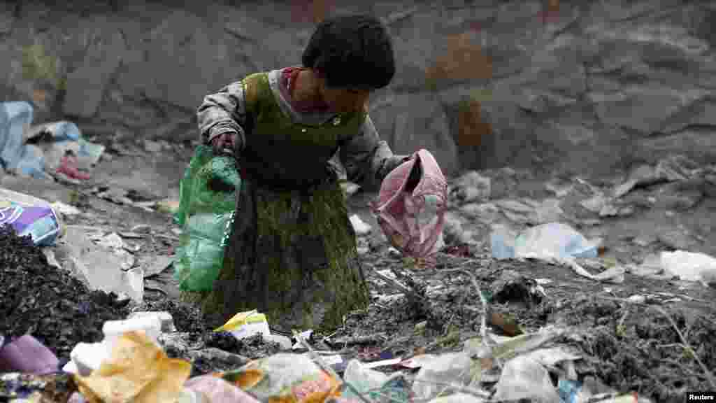 An Afghan girl searches for recyclable items at a rubbish heap on the outskirts of Kabul on April 26. (Reuters/Omar Sobhani)