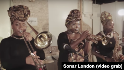 Richie SeivWright (trombon), Sheila Maurice-Grey (trompetă, șefa grupului), Cassie Konoshi (saxofon)