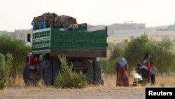Сирийцы, бежавшие из охваченного боями города Алеппо, готовят себе еду рядом с грузовиком. 19 октября 2015 года.