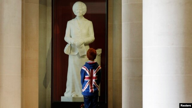 A boy stands in front of a statue of former British Prime Minister Margaret Thatcher on display in the Guildhall Art Gallery in London.
