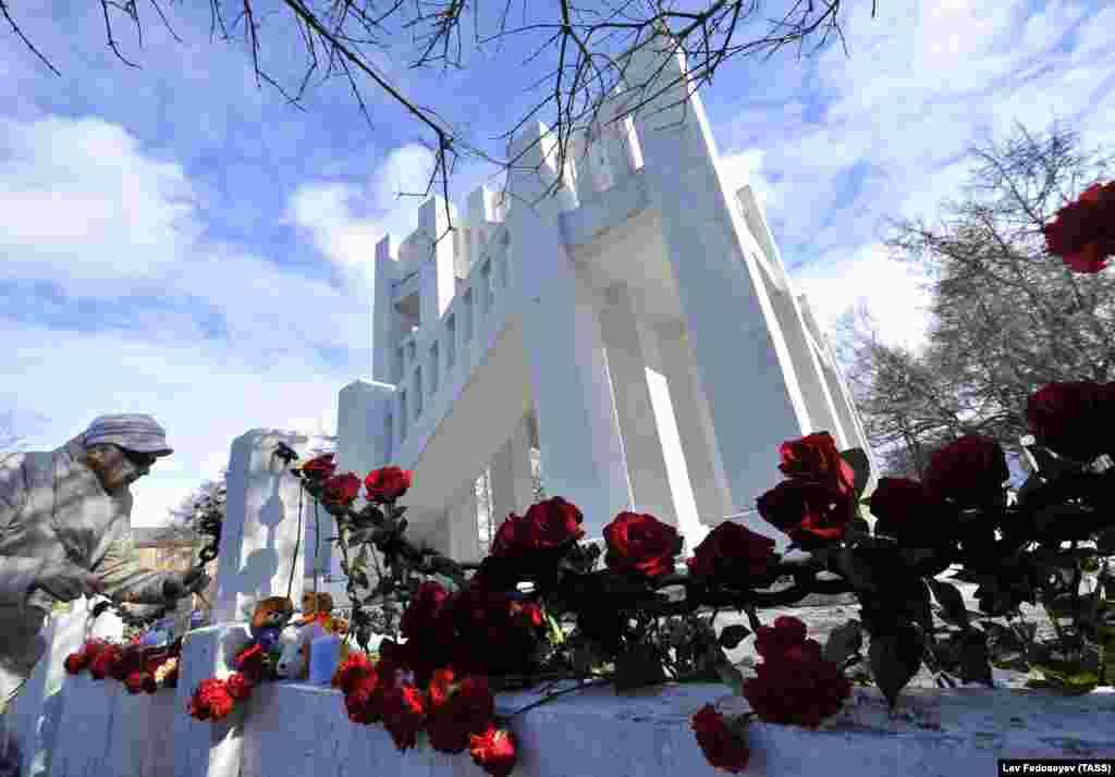 Женщина кладет цветы к стихийному мемориалу у памятника жертвам интервенции в Мурманске – в память о погибших в аварии