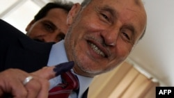 Libya -- Libyan National Transitional Council chairman Mustafa Abdel Jalil shows his ink-stained finger after voting at a polling station in the eastern city of Al-Baida during Libya's General National Congress election, 07Jul2012
