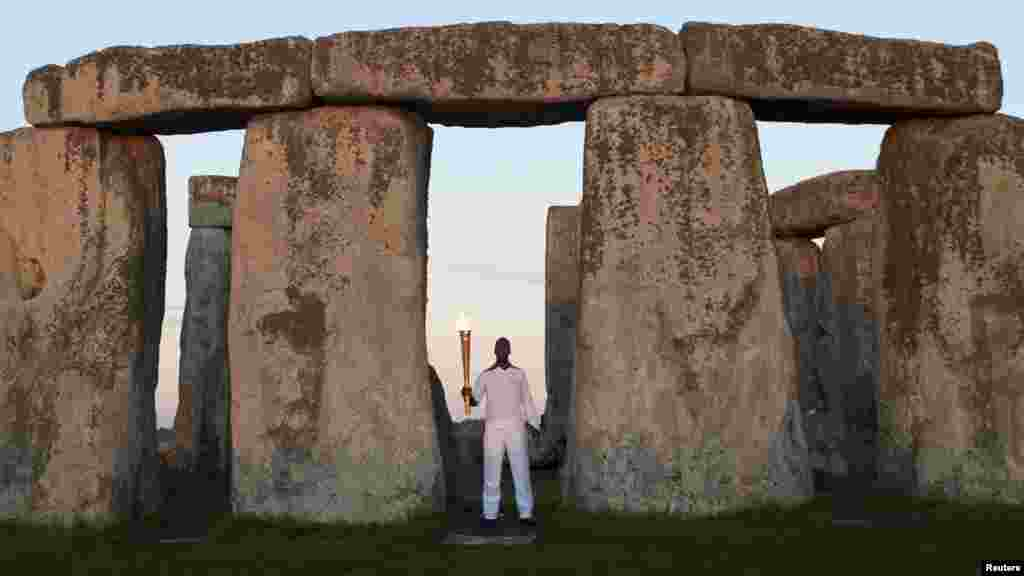 Former U.S. athlete Michael Johnson holds the Olympic Torch aloft at the Stonehenge World Heritage in Salisbury, England, on July 12. (REUTERS/Kieran Doherty)