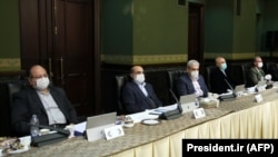 Cabinet members wear a protective mask and gloves as means of protection against the cornonavirus COVID-19, during a cabinet meeting in the capital Tehran, March 11, 202