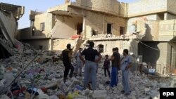 Men inspect the debris of houses after an apparent air strike by the Iraqi Air Force in Fallujah on September 1.