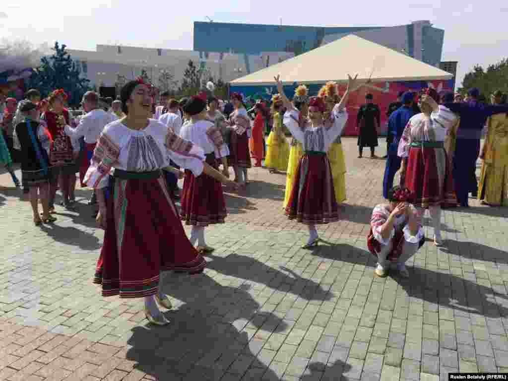 Женщины в национальных украинских костюмах танцуют в центре Астаны.