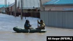 Люди на надувной лодке в затопленном паводками районе Актобе. 16 апреля 2017 года.