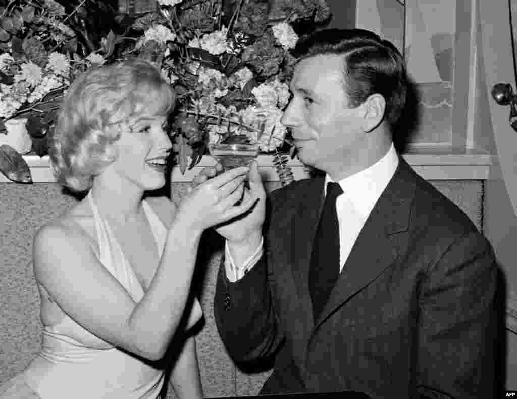 "Monroe shares a glass of champagne with French actor and singer Yves Montand in Hollywood after the screening of their movie ""Let's Make Love,"" directed by George Cukor, in 1960."
