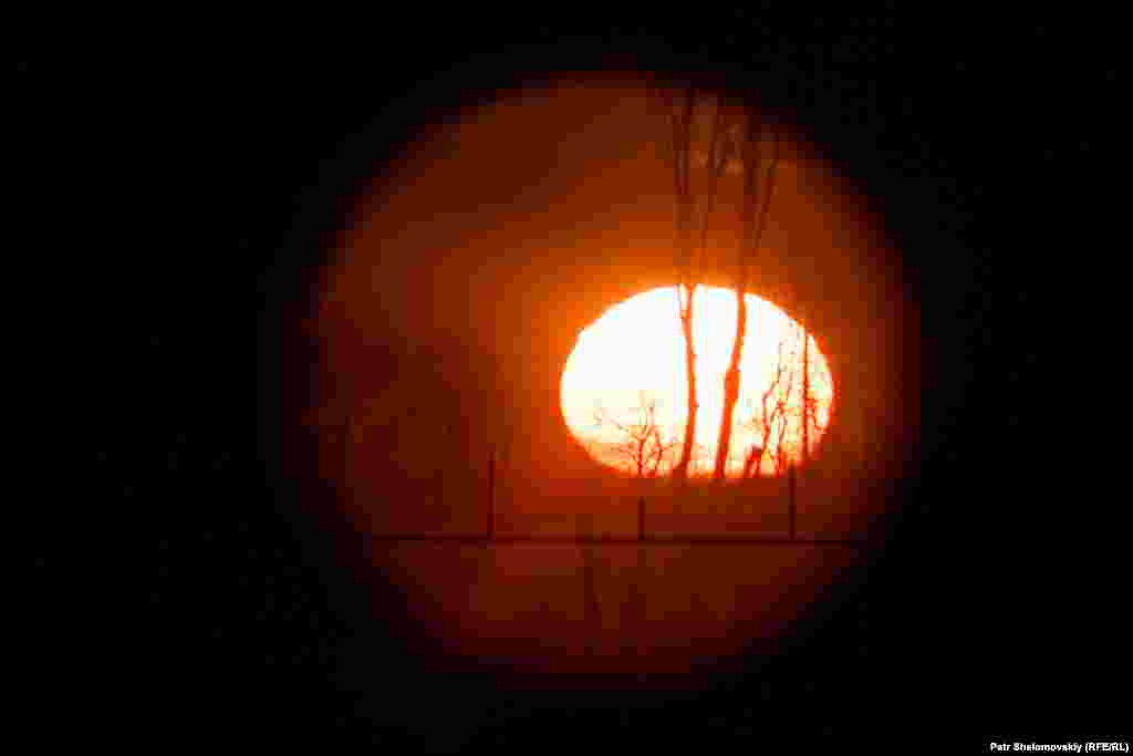 The rising sun is seen through a military scope from a Ukrainian army position near Zaytseve.