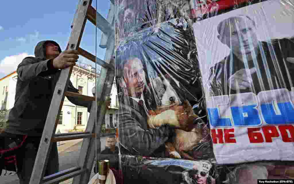 A man climbs a ladder near a Moscow storefront with T-shirts displaying portraits of Russian President Vladimir Putin. (epa-EFE/Yuri Kochetkov)