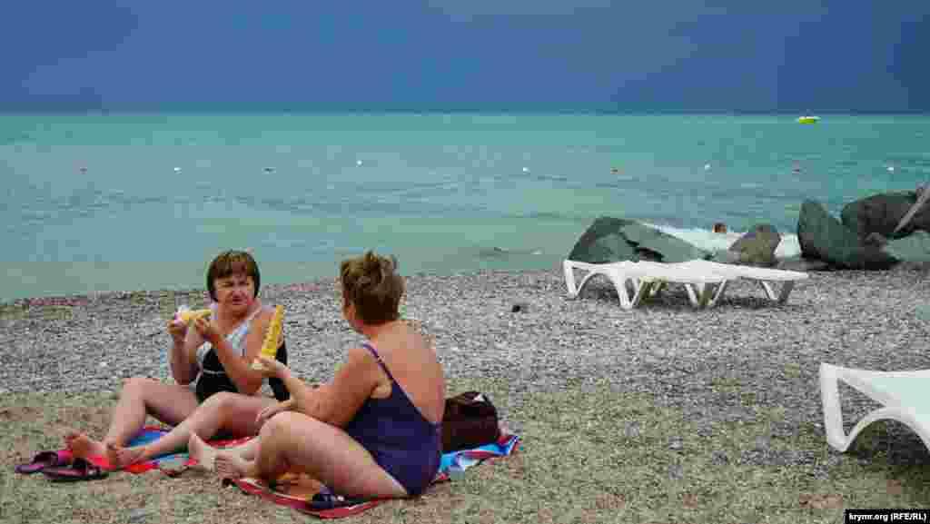Пока отдыхающие едят вареную кукурузу, на пляж надвигается грозовая туча