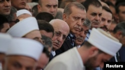 A group of imams bow their heads next to Turkish President Recep Tayyip during a funeral service for victims of the thwarted coup in Istanbul.
