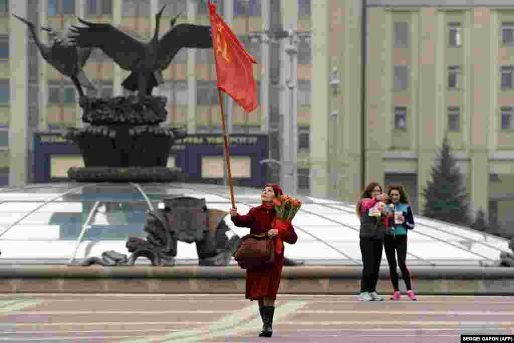 An elderly woman carries a Soviet flag on Independence Square as she celebrates International Women's Day in Minsk on March 8. (AFP/Syarhey Gapon)