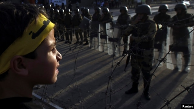 A boy, with supporters of the Muslim Brotherhood and ousted Egyptian President Muhammad Morsi, stands in front of army soldiers and riot police, during a protest in Cairo on October 4.