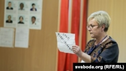 Старшыня камісіі паказвае бюлетэнь Дзяніса Краўчука, якія скарыстаўся кодам 000-179, каб прагаласаваць тройчы