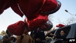 Сотрудник пакистанской полиции (справа) рядом с торговцами воздушными шарами в форме сердец. Исламабад, 13 февраля 2017 года.
