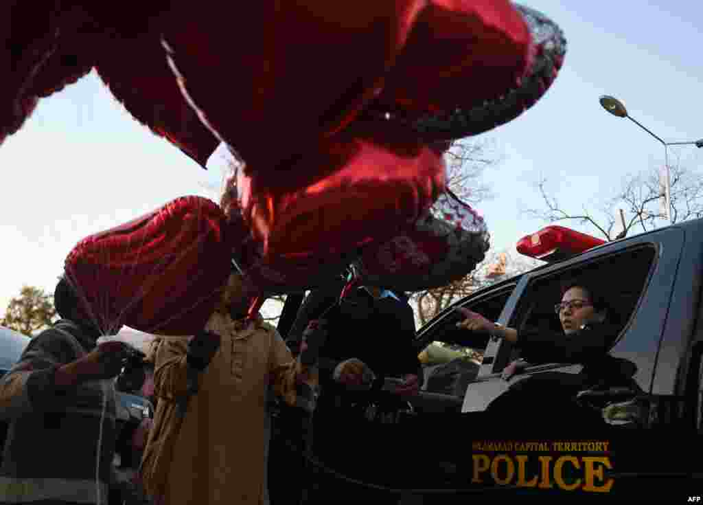 A Pakistani police officer, right, gestures as she buys a heart-shaped balloon at the flower market ahead of Valentine's Day, in Islamabad on February 13.