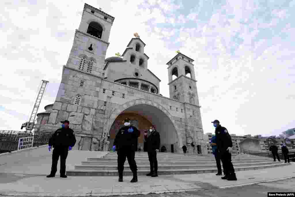 Police officers watch the entrance of the Cathedral of the Resurrection of Christ in Podgorica, Montenegro, on April 19 as Serbian Orthodox priests hold a morning Easter liturgy without worshipers.