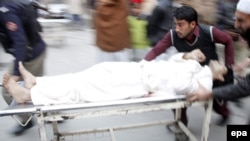 People stretcher an injured victim away from the scene of a suicide bomb blast in Peshawar on January 30.