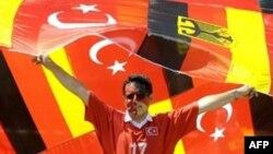 Navijač sa turskim i njemačkim zastavama