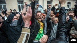 Pro-Russia militants, who had been detained during an attack on a Ukrainian unity rally on May 2, react after being freed following the storming of a police station in Odesa on May 4.