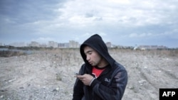 A Tajik migrant worker in Russia texts a message home.
