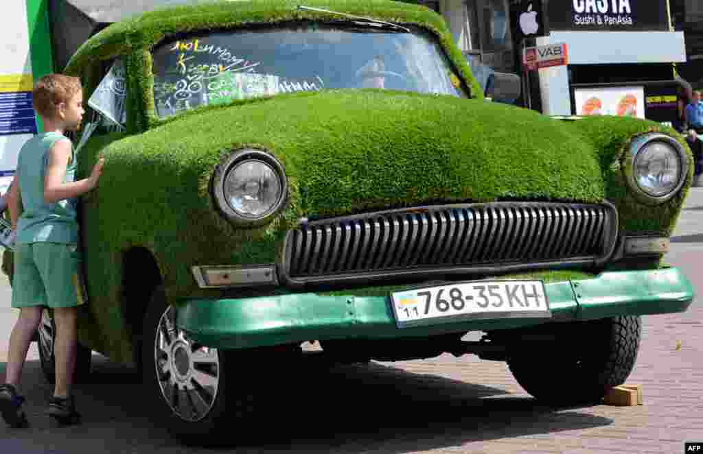 A Ukrainian boy looks at a GAZ-21 Volga car decorated with grass and parked in Kyiv. (AFP/Sergei Supinsky)