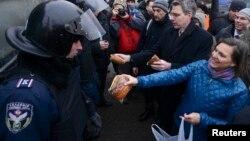 Ukrainë - Asistentja e sekretarit amerikan të shtetit për Evropë dhe Euro-Azi Victoria Nuland (D) dhe ambasadori i ShBA-së Geoffrey Pyatt (2-ti D) i shpërndan bukë policisë në Sheshin e Pavarësisë të Kievit, 11 dhjetor, 2013