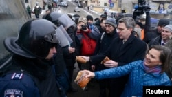 Заступник держсекретаря США Вікторія Нуланд і посол США в Україні Джеффрі Пайєтт пропонують випічку курсантам Академії внутрішніх справ, яких силовики залучили до «охорони громадського порядку», Київ, 11 грудня 2013 року