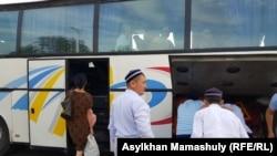 Арысқа қайту үшін автобусқа отырып жатқан тұрғындар мен оларға көшуге көмектесіп жүрген молдалар. Шымкент, 28 маусым 2019 жыл.