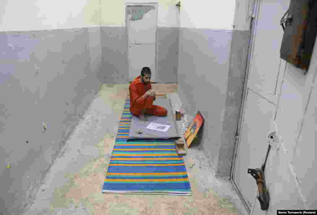 Abed El-Hamed Atiya, an Iraqi prisoner suspected of being part of the Islamic State group, sits next to a picture he drew inside a prison in Hasaka. He is kept apart from other prisoners, some of whom strongly object to his art.
