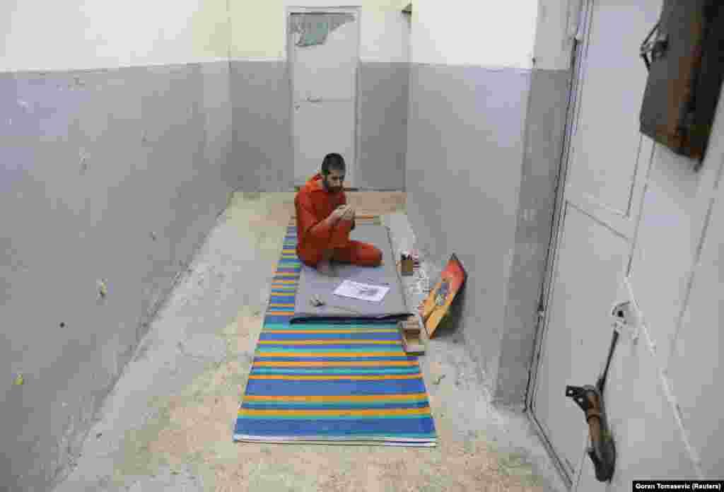 Абед Эль-Хамед Атия, иракский заключенный, рядом с изображением, нарисованным собственноручно в тюрьме. Он содержится в отдельной камере, поскольку некоторые заключенные выступают решительно против его искусства.