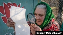 Възрастна жена разглежда бюлетината в избирателна секция близо до Донецк.
