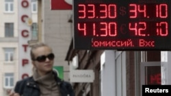 A woman passes by a sign displaying currency exchange rates in Moscow on June 1.