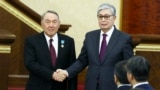 KAZAKHSTAN -- Acting Kazakh President Qasym-Zhomart Toqaev and outgoing Kazakh President Nursultan Nazarbaev shake hands after an inauguration ceremony in Astana, March 20, 2019