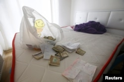 Foreign currency banknotes and various documents are seen in the bedroom where the alleged attacker was caught by Turkish police in the Esenyurt neighborhood of Istanbul.