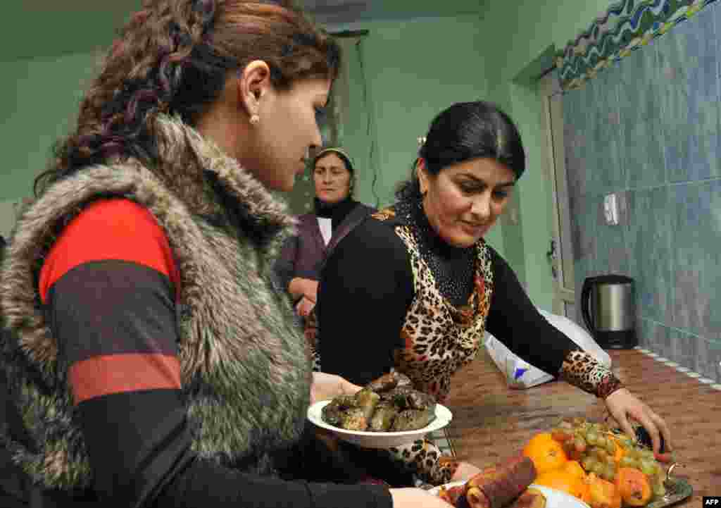 Yazidi women prepare dinner at their home.