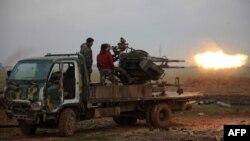 Сирияның Алеппо қаласының маңында әскери қарудан оқ атып жатқан адамдар. 14 қаңтар 2016 жыл. (Көрнекі сурет.)