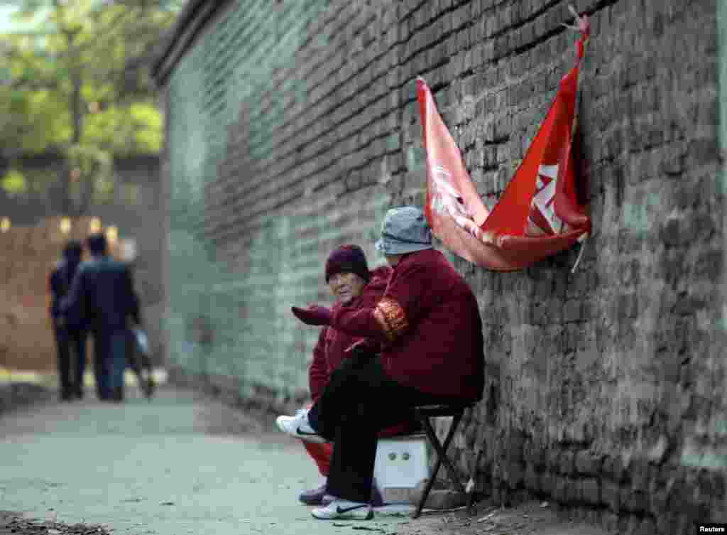 Elderly women with red armbands, identifying them as security volunteers, chat as they sit to watch over a traditional alleyway in central Beijing.