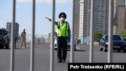 Темір шарбақпен қоршалған Тәуелсіздік алаңы маңында тұрған полиция қызметкері. Нұр-Сұлтан, 6 маусым 2020 жыл. Көрнекі сурет.