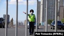 Сотрудник полиции с жезлом за металлической оградой. Нур-Султан, 6 июня 2020 года.