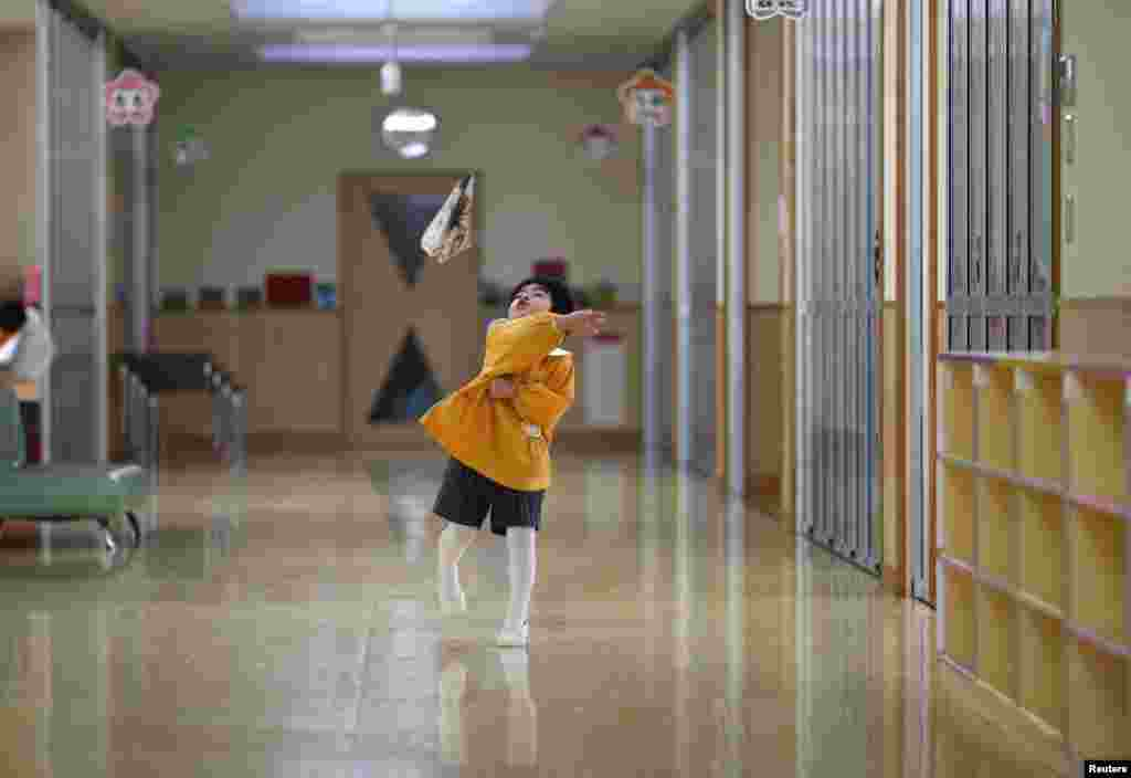 A boy plays with a paper plane in the corridor of a kindergarten in Koriyama.