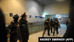 Police officers look (L) at Russian Federal Security Service (FSB) agents (R) rushing inside Moscow's Domodedovo international airport on January 24, 2011, shortly after an explosion.