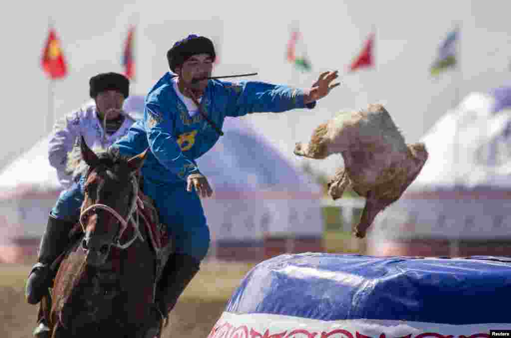 A rider from the Kazkah team drops the headless goat into the container for a score against Russia during the first Asian kokpar championship.